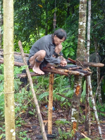 Penan elder making a blow pipe for hunting