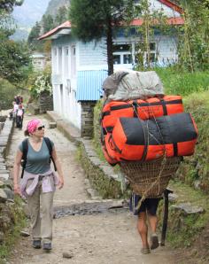 A Nepali Porter carrying trekking group gear (not an Adventure Alternative group)